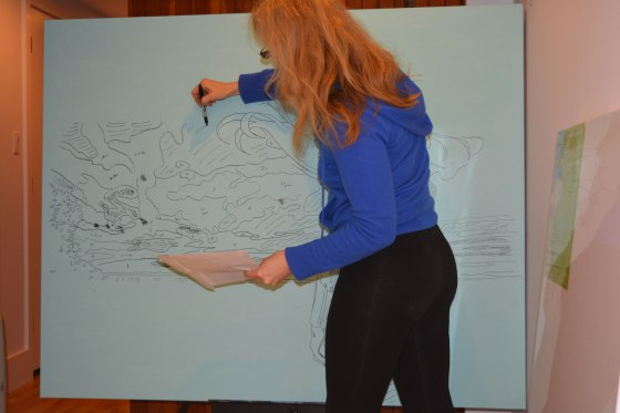 Artist Darlene Baker drawing on large canvas.