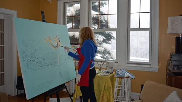 Artist Darlene Baker oil painting a large Millennial Mom canvas with a snowy New Brunswick day in the window behind her.