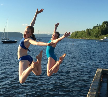 Artist's two daughters joyfully jumping mid-air off the dock into the river.