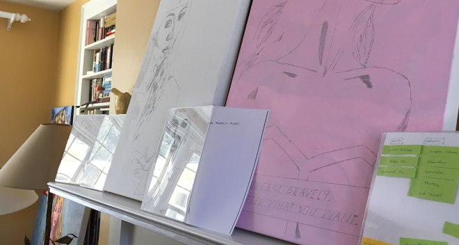 Canvases and sketches lined up on a mantel.